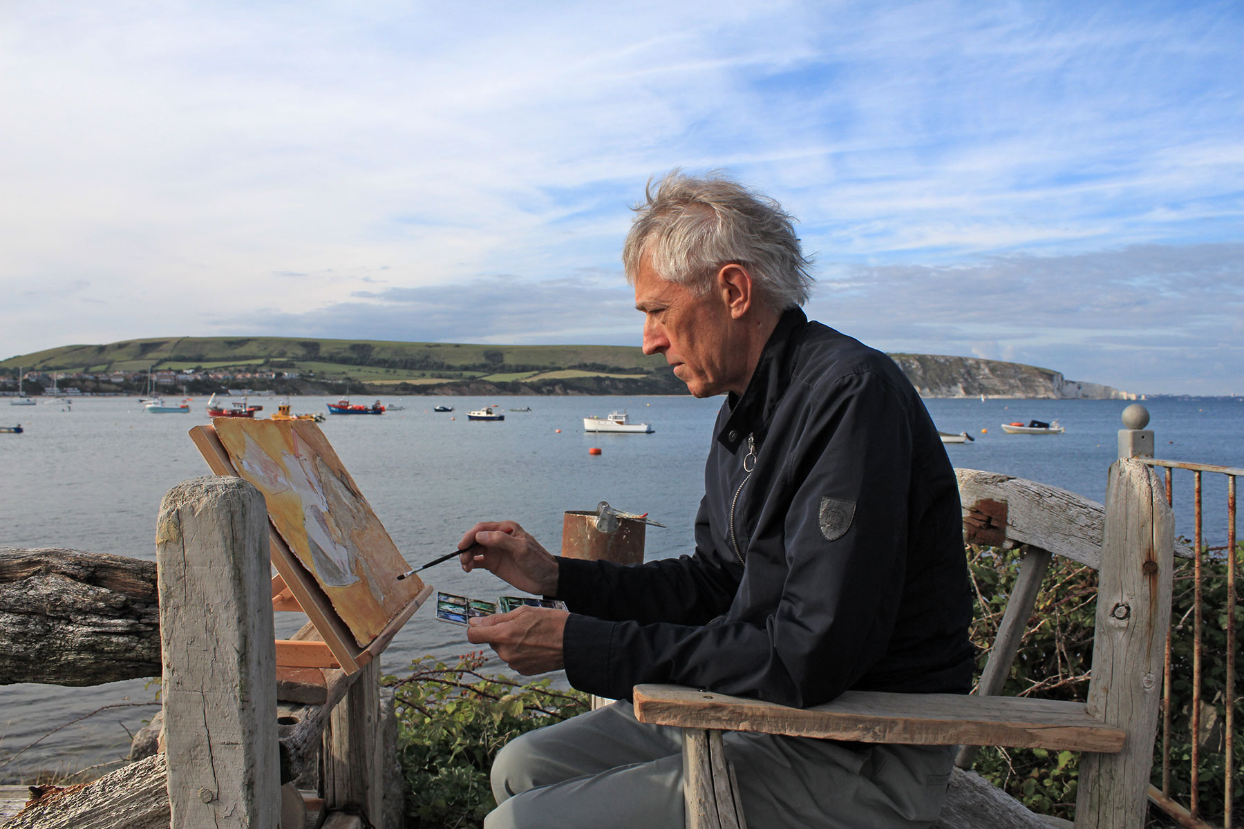 Jeremy Gardiner painting plein air with brush and watercolours, Ballard Point in the background